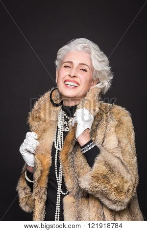 Portrait of senior rich woman in expensive fur coat happy smiling for photographer. Beautiful woman toothy smiling.