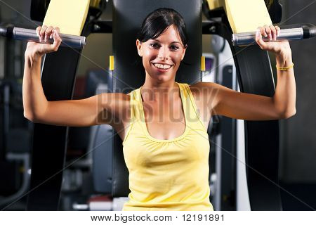 Very fit and beautiful young woman in a gym working out and lifting weights on an exercising machine