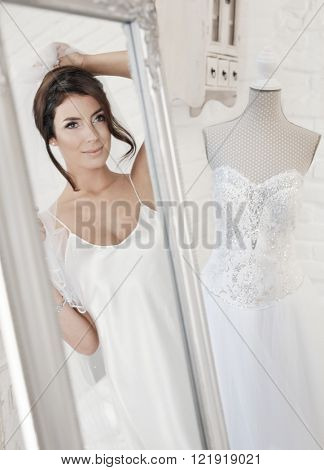 Beautiful bride dressing up on wedding-day, looking at herself in mirror.