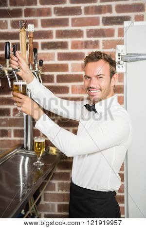 Handsome bar tender pouring a pint in a pub
