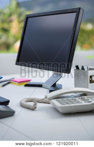 Computer and telephone on desk in office