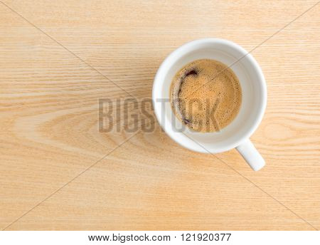 Half espresso coffee in a cup on wooden textured table