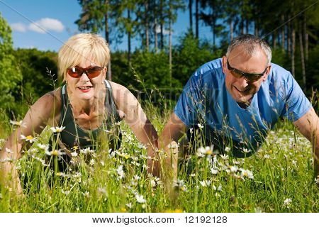 Mature or senior couple in jogging gear doing sport and physical exercise outdoors, pushups
