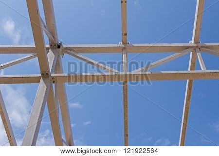 New structure girders on skeleton of the future roof against the blue sky.
