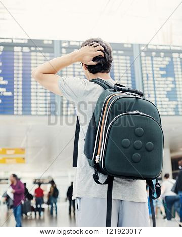 Back view of confused college student traveling with backpack, standing with hand on his head and checking information about his flight on airport timetable - travel concept