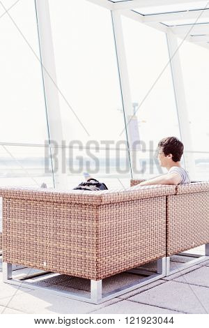 College student chilling out in airport departure lounge: sitting on armchair and enjoying runway through huge window - travel concept
