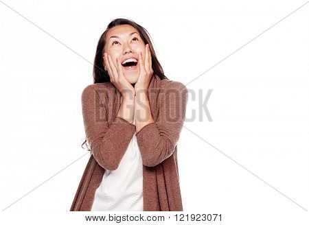 Young surprised asian woman wearing brown cardigan, standing with hands on her head and looking up with wide open mouth isolated on white background - astonishment concept