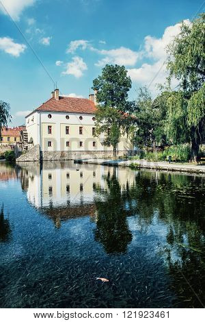 Mill house is mirroring in the water level of the lake Tapolca Hungary central Europe. Golden fish.