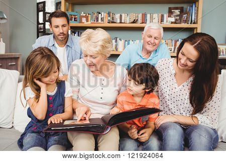 Smiling family with grandparents holding photo album at home