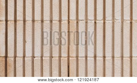 surface of an old wall of beige colored shaped concrete blocks with coarse seams and joints with vertical stripes outdoors