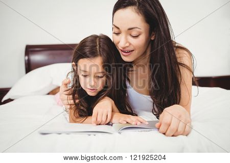 Close-up of daughter reading book with mother on bed at home