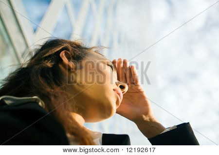 young professional woman looking far away in front of a modern office building, presumably at new career options