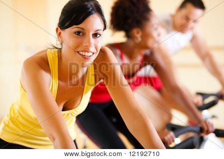 Three People In The Gym exercising on cycles