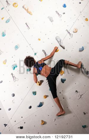 Woman (African-American) exercising at a climbing wall in a gym