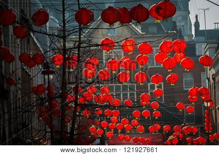 London United Kingdom - March 13 2016: London Chinatown is decorated with traditional red Chinese lanterns for Chinese New Year. The lanterns are glowing in the evening light catching the light.