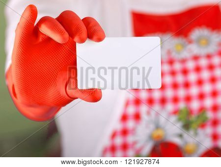 Close up of female hand with safety glove holding and showing blank business card against her body with red apron