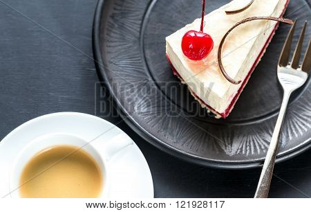 Raspberry cheesecake decorated with cocktail cherry with cup of coffee