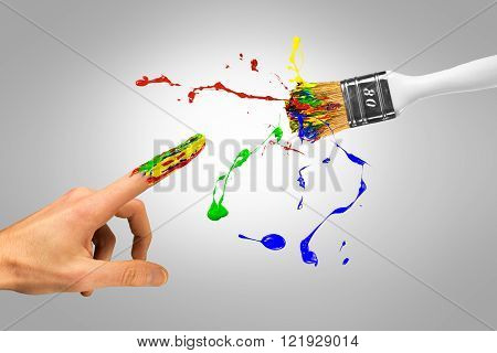 Miracle creation of creative man by colorful paintbrush on a grey background