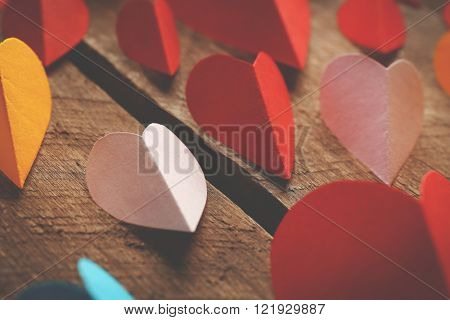 Varicolored paper hearts on wooden background, close up