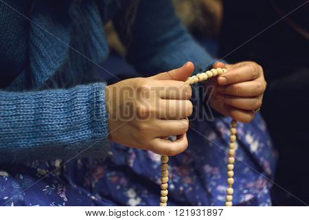 Woman holding Indian beads at ethinic Indian holiday
