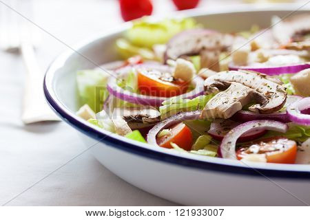 Healthy fresh summer salad with letucce radish cherry tomatoes red onion and champignons with italian herbs in a bowl on a table closeup