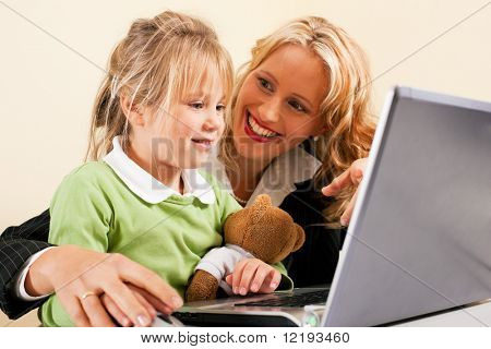 Family Business - telecommuter Businesswoman and mother showing her little daughter how these computer and internet things work