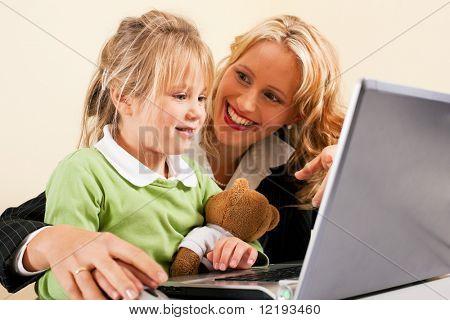 Empresa familiar - teletrabalhador empresária e mãe mostrando sua filhinha como estes comput