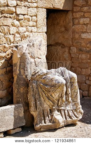 Ancient statue in Dougga Roman Ruins: A Unesco World Heritage Site in Tunisia. Ruins of the roman City of Dougga with the Capitol.