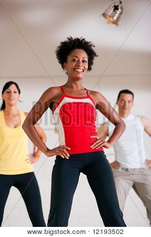 Group of three people in colorful cloths in a gym doing step gymnastics, a female instructor in front
