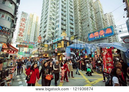 HONG KONG, CHINA - FEB 9: Crowd of people walking on busy market street with bright showcases of shops and malls on February 9, 2016. There are 1223 skyscrapers in Hong Kong.