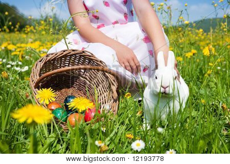 Child petting the Easter bunny on a spring meadow, eggs in a basket and lots of flowers also to be seen. It is not entirely clear whether the bunny enjoys the treatment