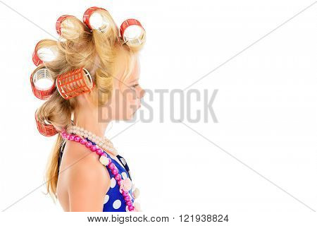 Funny little girl in her mother's hair curlers and polka-dot dress. Kid's fashion, cosmetics. Pin-up style. Isolated over white.