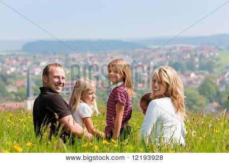 Happy family - mother, father, three children - sitting in a meadow in spring  or early summer, looking at the viewer, in the background is a village