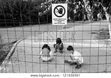 ATHENS, GREECE - SEPTEMBER 19, 2010: Children playing inside a fenced restricted area with a