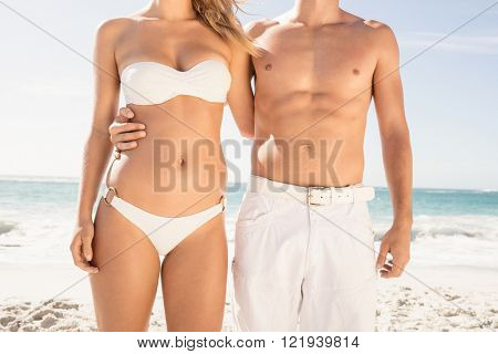 Young couple in beachwear embracing on the beach