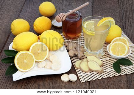 Natural cold remedy drink with vitamin c tablets, with fresh ginger, lemon, honey and cinnamon spice over oak background.