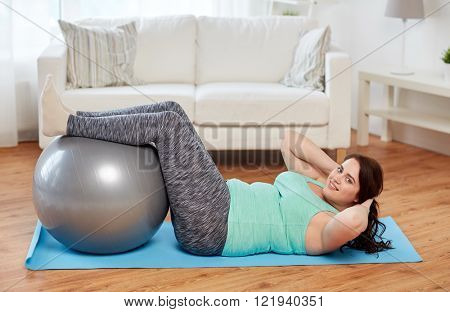 sport, people and healthy lifestyle concept - happy plus size young woman exercising with fitness ball on mat at home