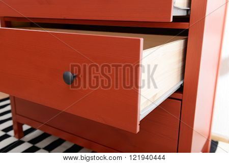 Open shelves of chest of drawers closeup