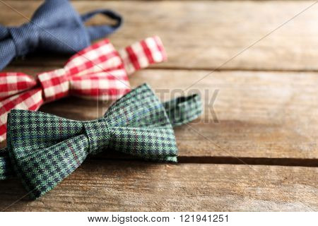 Different bow ties on wooden background