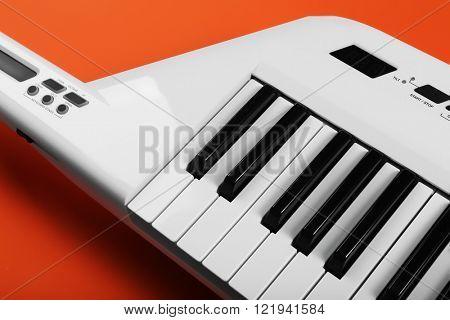 Keyboard of synthesizer on orange background