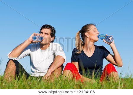Deporte joven pareja fue correr en un verde prado de verano pero está descansando ahora, reposición de sí mismos