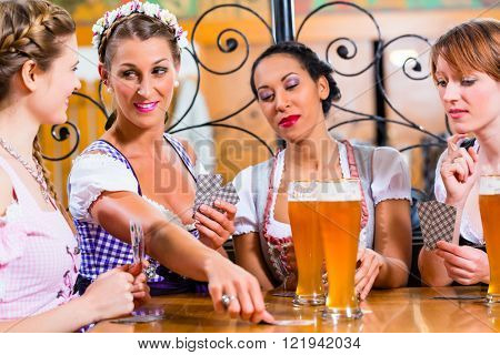 Friends playing cards in Inn or pub drinking beer