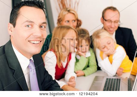 Family with their consultant (assets, money or similar) doing some financial planning, the consultant in front looking at the camera