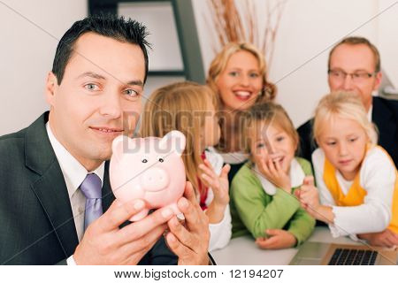 Family with their consultant (assets, money or similar) doing some financial planning - symbolized by a piggy bank in the front, the consultant in front looking at the camera