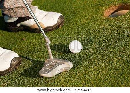 Golf player attempting the tee stroke in the teeing area (only legs of player to be seen, focus on ball)