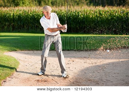 Mature or senior couple playing his ball out of a sand trap, ball in motion and lots of sand frozen (short shutter speed)