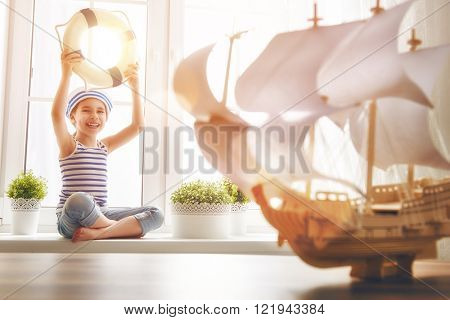 Adorable little child sitting on the window. Girl dreams of sea, adventures and travel. Girl has a toy ship.