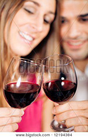 Joven pareja - hombre y mujer - en un restaurante en el tintineo de las copas de vino tinto; centrarse en las gafas