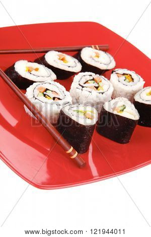 Maki Sushi : Maki Rolls and California rolls made of fresh raw Salmon, Tuna and Eel . on red dish with sticks isolated over white background