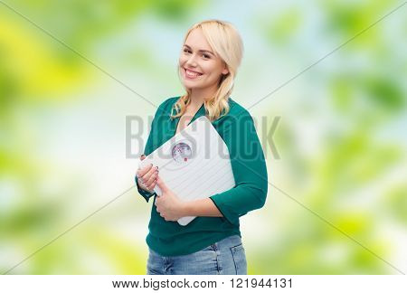 weight loss, diet, slimming, plus size and people concept - smiling young woman holding scales over green natural background